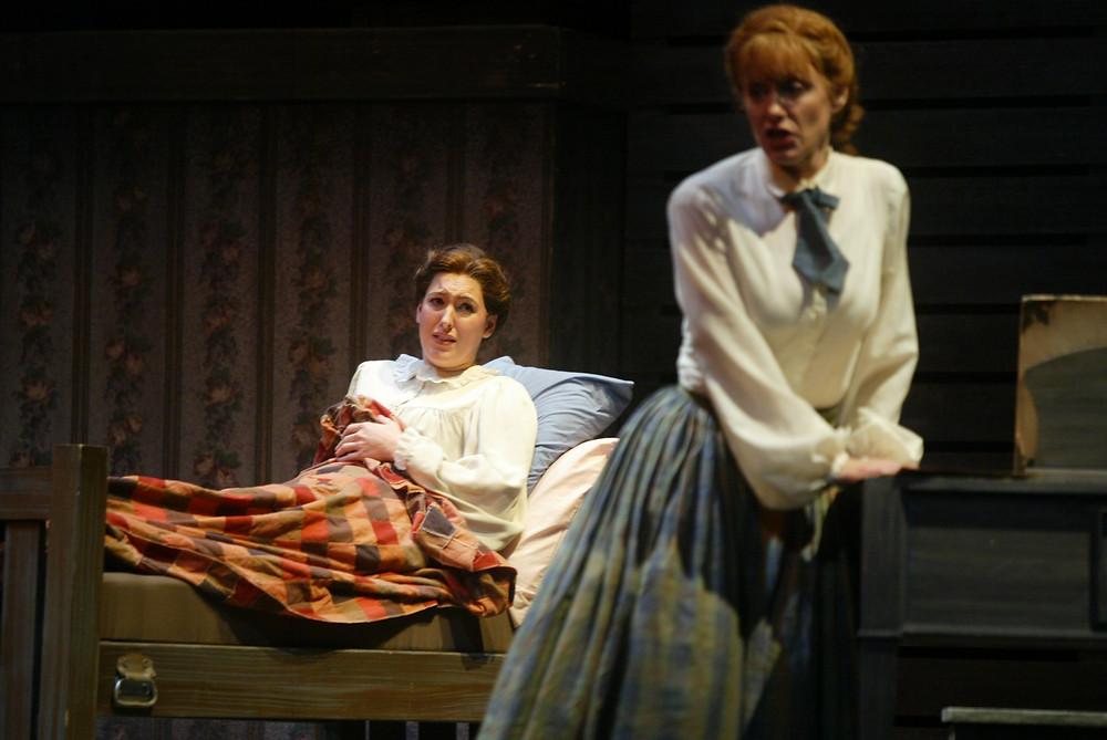 Jo March (Jennifer Dudley) at the bedside of a dying Beth March (Tawny Seward). Photo by Ellen Appel.