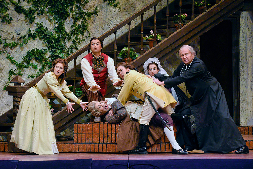 "Left to right, Rosina (Megan Marino), Figaro (Joo Won Kang), Dr. Bartolo (Kyle Albertson) pinned down by the group, Count Almaviva (Andrew Stenson), Berta (Maren Weinberger), and Don Basilio (Tyler Simpson), ""The Barber of Seville"" FWO 2016; photo by Karen Almond."