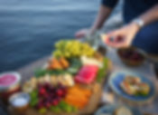 serving up some plates of jarred salmon on bruschetta, and various fruits and vegetables