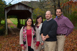 Family in front of covered bridge