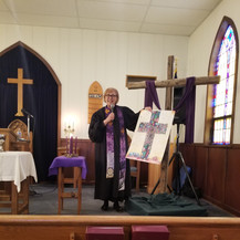 Pastor Cathy Manthei uses a poster from Rev. Koehn for the service.