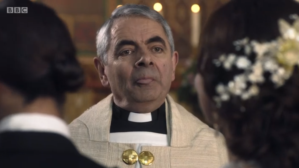 Rowan Atkinson as the bumbling Father Gerald who can't rap his head around same-sex marriage
