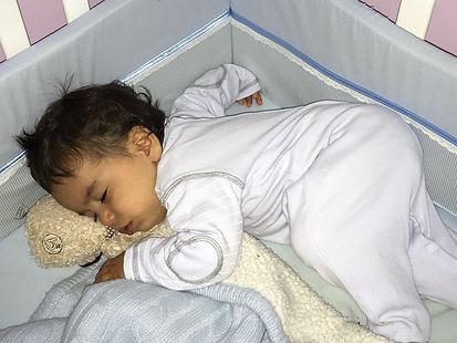 תינוק חמוד בן 8 חודשים ישן יחד עם חפץ מעבר - בובת דובי
