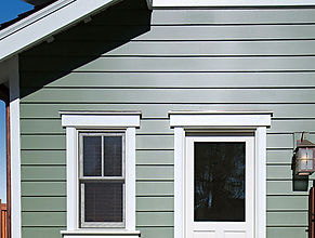 Image of painted green bodyguard siding an trim boards installed on house