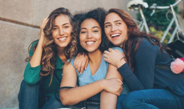 three smiling women sitting close to each other