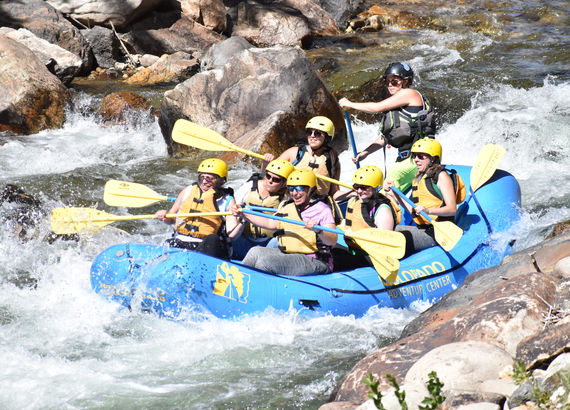 a group of people in a boat while water rafting