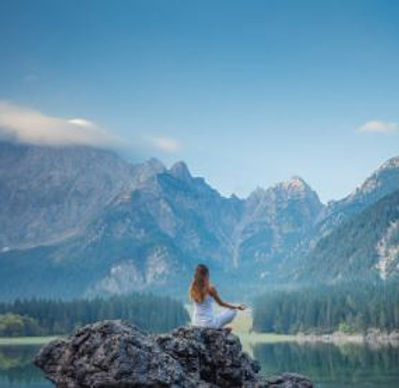 a woman sits in a big stone beside the lake facing the mountains