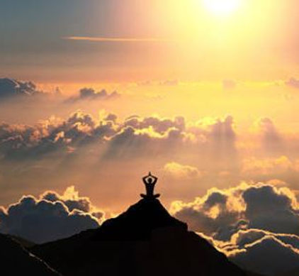 silhouette of a man of top of a mountain facing the sun and sea of clouds