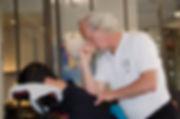 Massage assis en entreprise. Masseur au travail. Bien-être au travail. Massage du dos.