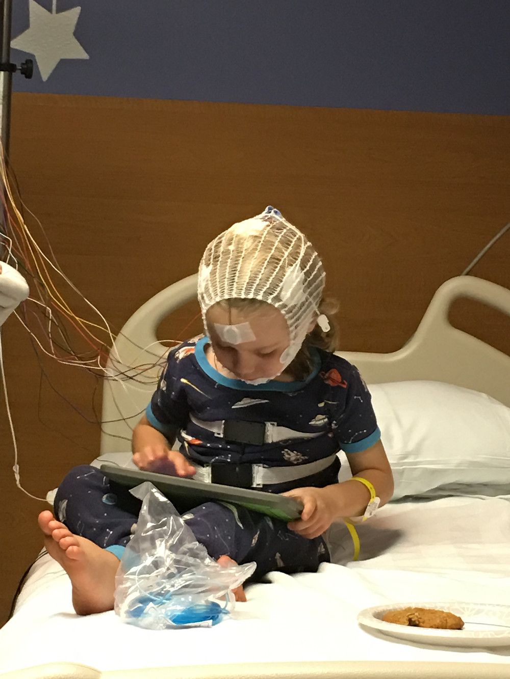 little boy hooked up to electrodes for sleep study. the boy sits on a hospital bed, looking down at an ipad with a cookie nearby.
