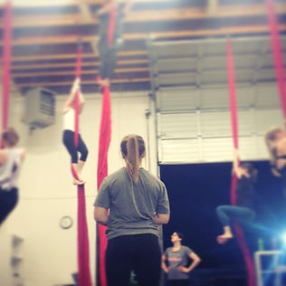 circus coach instructs students in aerials silks class at island circus space