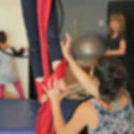 circus coach instructs student through acrobatic movements on the aerial silks at island circus space