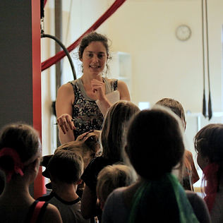 circus coach instructs a group of children at circus class at island circus space