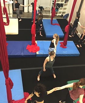 students stretch at the end of an aerial silks class at island circus space in victoria BC