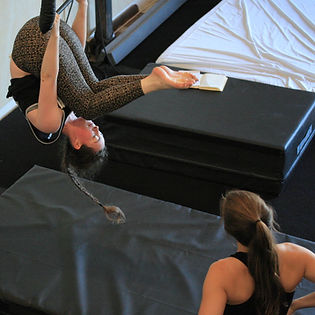 circus instructor guides a student through acrobatic skills on the trapeze at island circus space