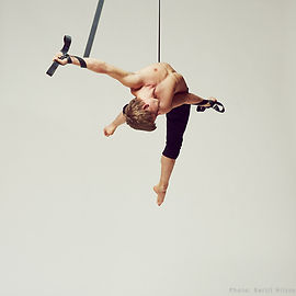 an aerialst performs on the aerial strap. Learn how to be an aerialist too at island circus space in victoria BC