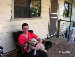 Image of - Cameon Skinner and his dog, Monty, on their veranda
