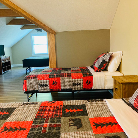 Large guest room with queen bed and 4 twin beds