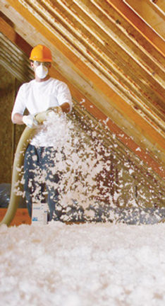 A member of the Insulating Salesw customer focused and professional installers blowing new R-38 insulation into a residential Cincinnati home.