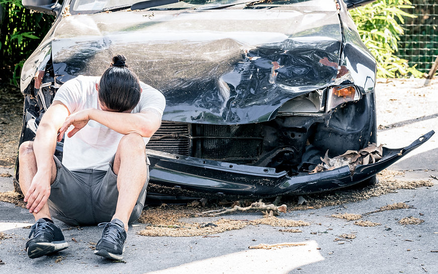man-crying-on-his-old-damaged-car-after-