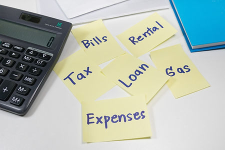 Sticky notes of monthly expenses and a c