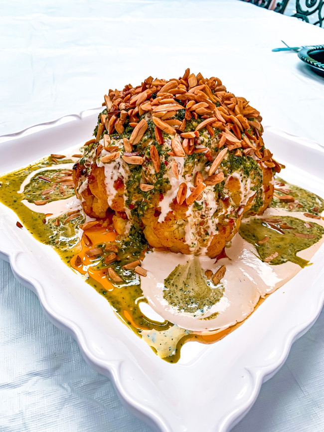 SPICY ROASTED WHOLE CAULIFLOWER WITH CILANTRO SAUCE, TAHINI SAUCE & CRUNCHY ALMONDS