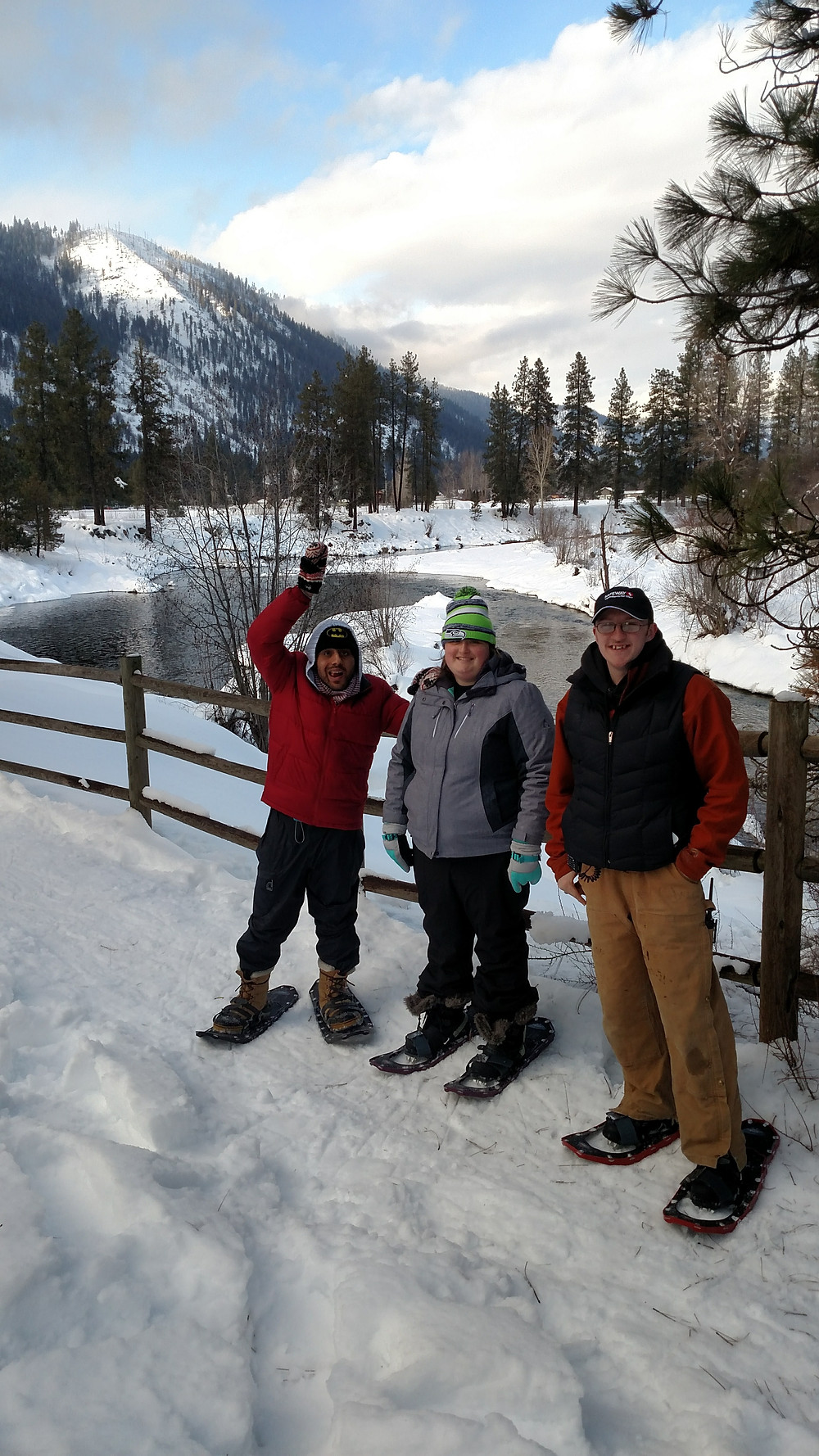 Three Developmentally Disabled Adults Snowshoe by a River.