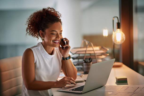 Une femme fixe un rendez-vous par téléphone en Anglais. Elle sourit.