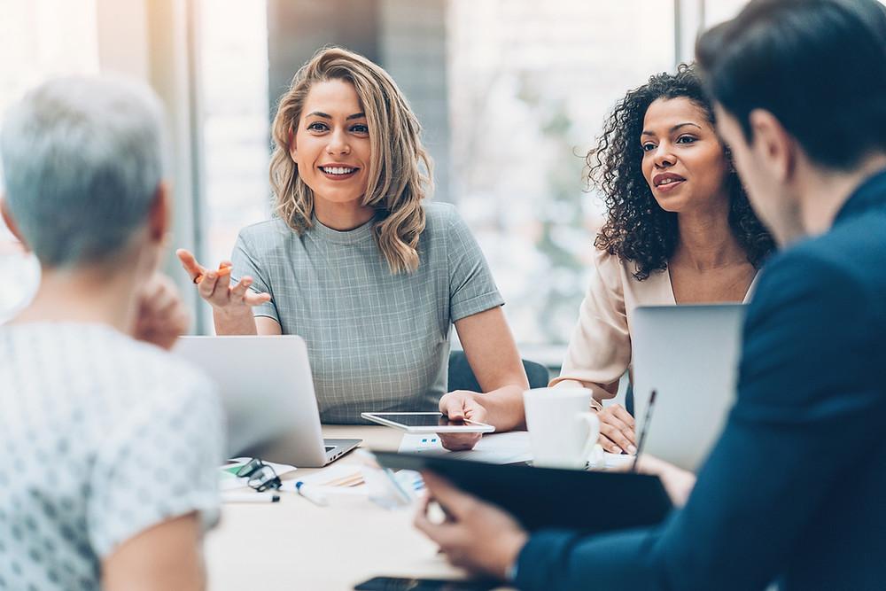 Quatre personnes sont en réunion, assis autour d'une table. Une femme s'adresse au groupe.