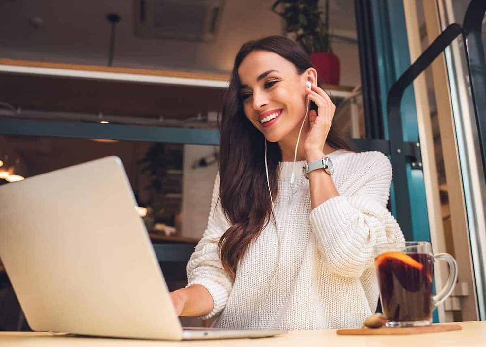 Un femme est connectée sur son ordinateur portable. Elle est sur son lieu de travail. Elle est en visioconférence. Elle porte des écouteurs. Elle sourit.