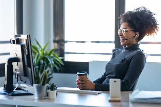 Une femme souriante est assise à son bureau devant un écran. Elle porte un casque et un micro, elle est en visioconférence.