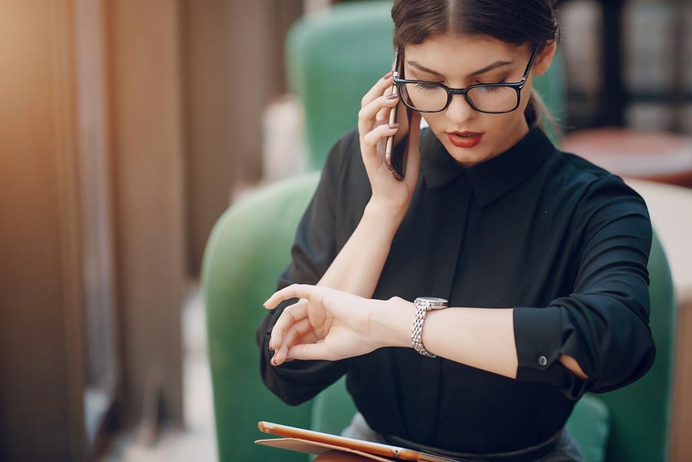 Une femme est au téléphone et regarde sa montre. Elle est assise et un dossier se trouve sur ses genoux. La femme se trouve sur son lieu de travail. Elle porte attention à sa montre, elle lit l'heure. Elle a un délai à respecter.