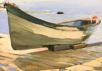A white rowing boat is shown in morning sun, moored on the dock at water's edge