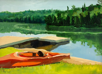 An orange sunlit kayak sits in the bright green grass by a dock in still water