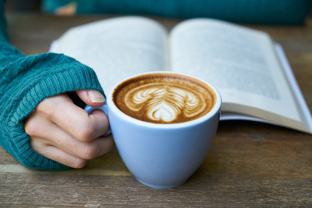 Hygge image of a cozy warm mug of coffee while reading a book