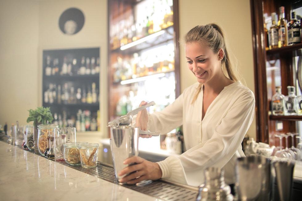 cheerful-female-bartender-making-cocktai