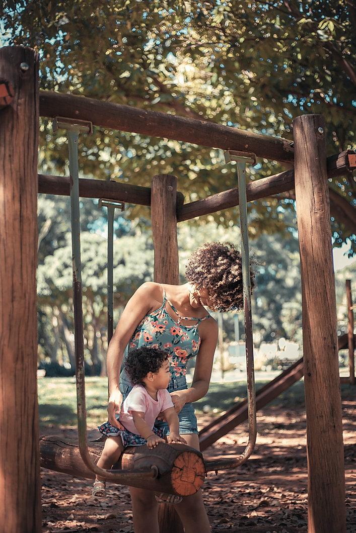 girl-riding-on-tree-log-swing-beside-wom