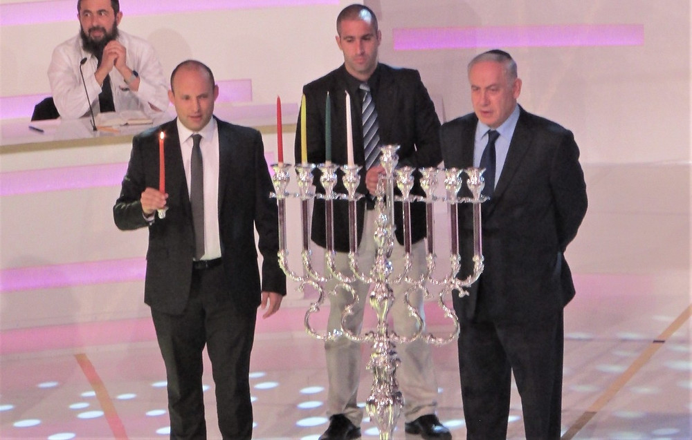 Prime Minister Benjamin Netanyahu and Education Minister Naftali Bennett Light a Menorah  by עדירל, [CC BY-SA 4.0], via Wikimedia