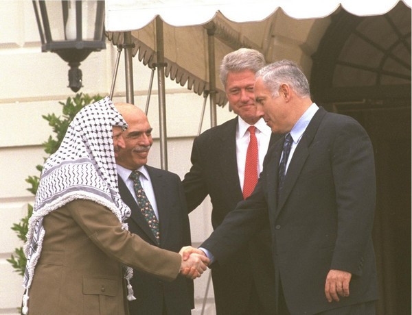 Binyamin Netanyahu shakes Yasser Arafat's hand at the White House as Bill Clinton and King Hussein watch (Image credit: Avi Ohayon/Government Press Office of Israel)