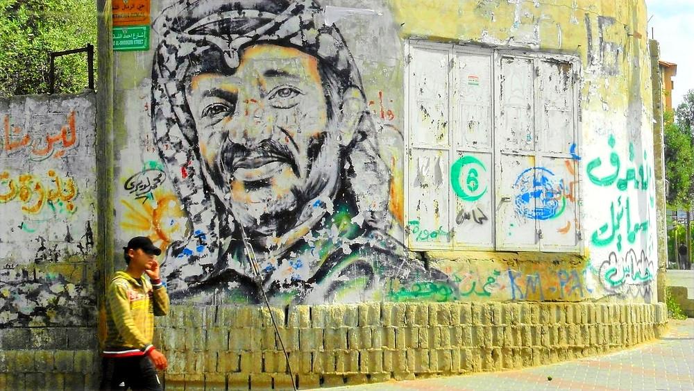 Illustration: Wall painting of Yassar Arafat by Mujaddara [CC BY-SA 3.0] via Wikimedia