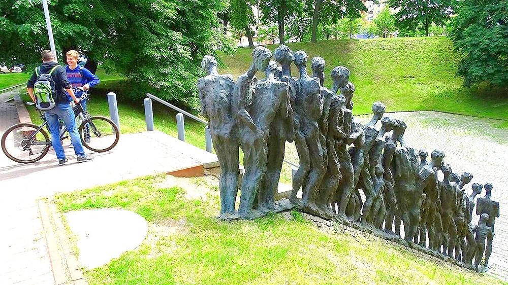 Illustration: Boys In Minsk Stand Next To Zaslavskaya Memorial To The Murdered Jews by Adam Jones [CC BY-SA 2.0] via Wikimedia