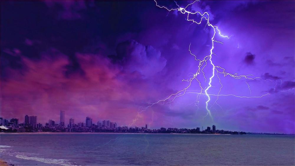 Illustration: Lightning Strikes Near Ocean by Guilherme via Pexel [Free to Use Pexels License)