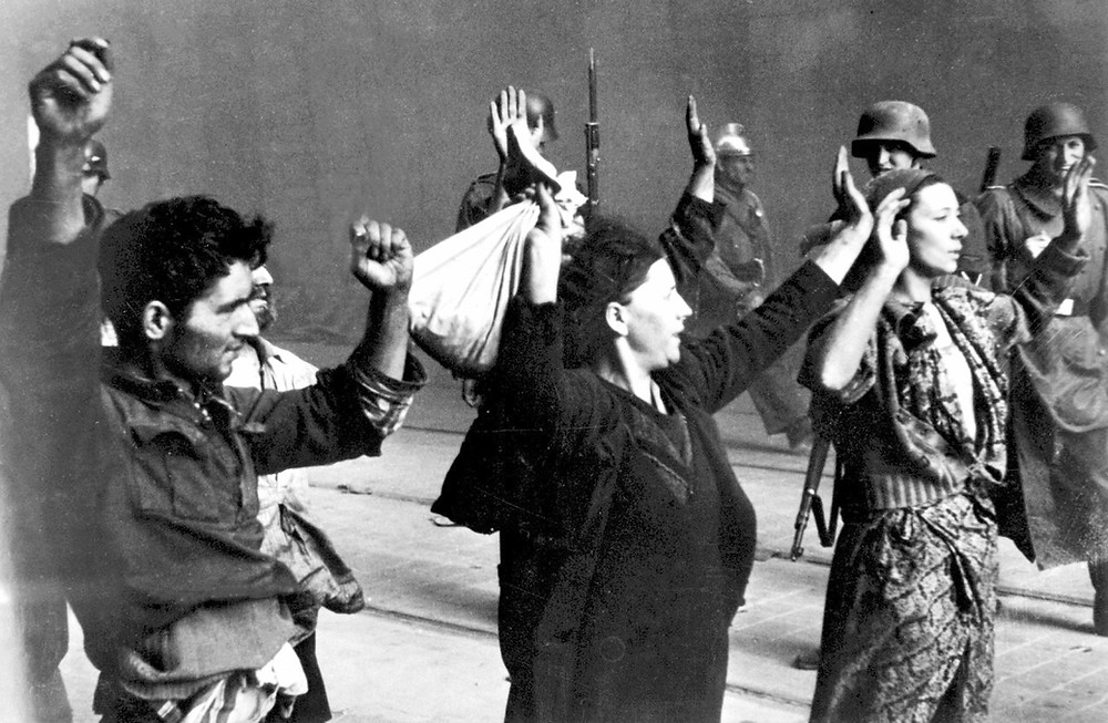 Illustration: Warsaw Ghetto Fighters Apprehended by Nazi Troops by Unknown (Franz Konrad confessed to taking some of the photographs or photographers from Propaganda Kompanie nr 689) [Public Domain] via Wikimedia