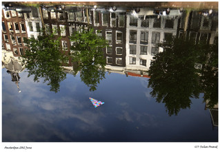 Reflection of row houses in Amsterdam canal