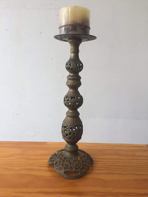 Tall ornate metal candlestick.