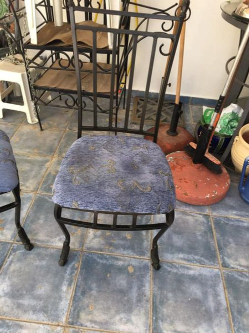 Two wrought iron chairs with blue upholstery