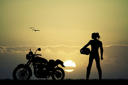 Female rider with helmet next to a classic motorcycle