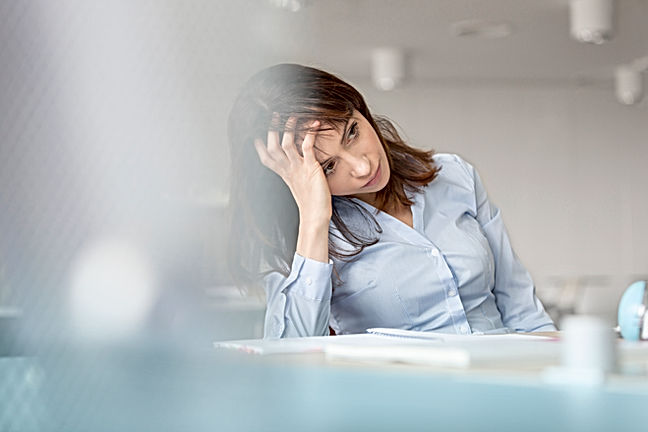 young woman resting head on hand considering calling her employee assistance helpline