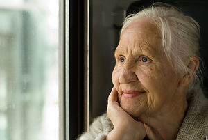 Lovely grandmother looking in a window,