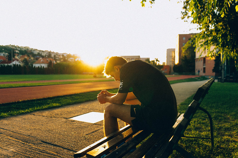 man-sitting-on-bench-near-track-field-wh